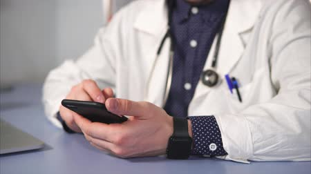 лечит : close up shot of the therapist hands, who uses the phone to find the composition of medicines. A man in a white robe holds a mobile phone and uses a touch screen