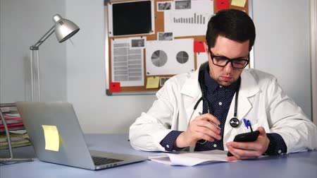 лечит : A serious doctor in a white coat and stethoscope on the neck, writes the patients tests to the form, they are stored in the mobile phone. A man in glasses sits at the table, where is his laptop