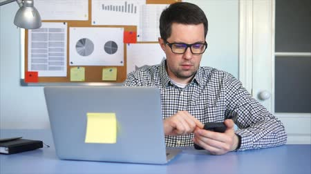 compares : Adult manager compares the data on the mobile phone with the numbers on the laptop. A man looks at the monitor of laptop and prints on the keyboard the result found in the Internet in the smartphone. Stock Footage