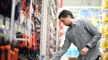 nákupy : Scene in hardware store. Customer chooses tools. He looking on the raw of tools and takes screwdriver and wrench. Dostupné videozáznamy