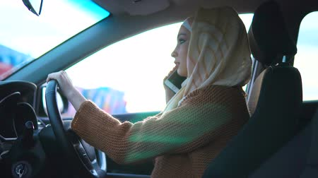 usual : A young modern Arab woman is talking on a new mobile phone, a Muslim in hijab is driving a right-hand drive. The usual life of a progressive woman driver Stock Footage