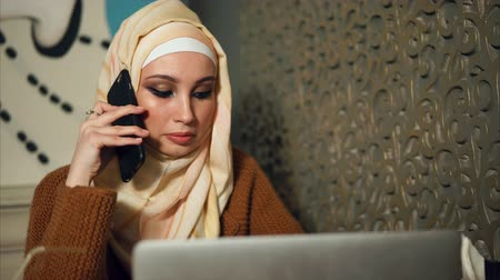 ислам : Young Middle Eastern woman talking on business on mobile while using laptop in cafe. Lifestyle of modern Muslim Women Стоковые видеозаписи