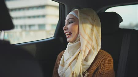 ислам : Young happy Middle Eastern woman traveling by taxi. She looking at the city through the window and enjoying the ride