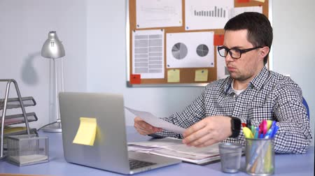 zdůraznit : The head of a small firm checks the documents with a serious look, emphasizing the important points. A man is sitting in the office at the desk with a laptop.