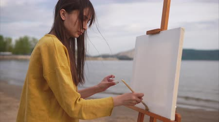 şövale : A young and creative woman artist prepares the canvas with a large brush and mortar. With rapid movements, the artist applies a solution to the canvas, which stands on the easel in the open air Stok Video