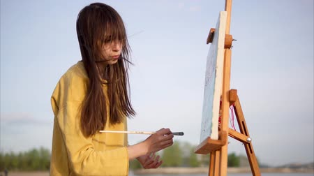 şövale : Woman artist painting with oil on canvas en plein air. Young impressionist creating landscape working outdoor by the lake