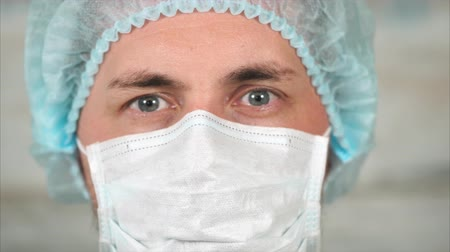 средний возраст : close up shot of a portrait of a middle-aged man is a person who looks like a surgeons doctor or a patient in a face mask, persons with a hat on his head