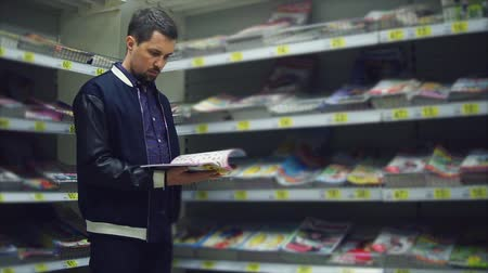 palavras cruzadas : Man standing among the shelves with magazines in the supermarket and looking through the one with crossword puzzles