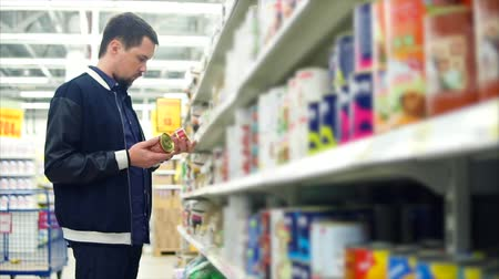 evcil hayvanlar : Man in the supermarket shopping in the section of pet supplies, he comparing two food cans