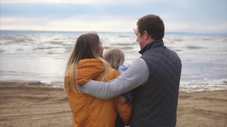 bakıyorum : Happy young family. Man with woman and little girl standing on the ocean shore and lookin on horizont Stok Video