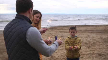 bengali : A young mother, her adult husband and their son lit the Bengal lights near the sea, a happy family is standing on the beach in warm clothes Stock Footage