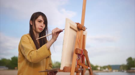 artistas : Woman painter working en plein air. She painting from nature in impressionism art style