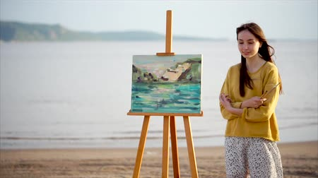 şövale : Young woman artist and her canvas painted en plein air against bright sunlight, water and green nature