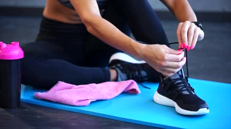 krawat : close up shot of at the womens athletic legs, who ties up the shoelaces on sports sneakers, the lady sits on a mat for streching, next to her stands a bottle of drink Wideo