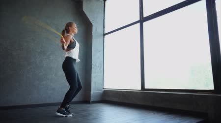 lift ups : An attractive and adult woman in a sports suit jumps on a rope, the sportswoman warms up the body before strength training in the fitness club