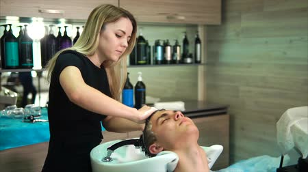 tüyler : The blonde hairdresser washes the head of the man with shampoo, the hair stylist is massaging to make the client enjoy the service and service of the fashion spa center