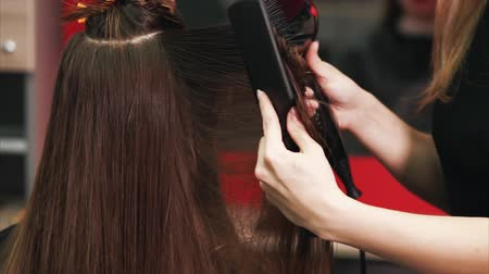 tmavé vlasy : close up shot of the hairdressers hands, who dries dark and long hair with a hair dryer and comb, the beauty salon client is waiting for the completion of the image change