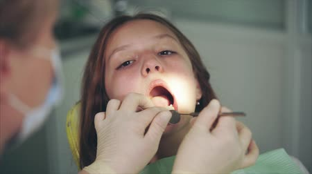 yenirce : Cleaning of teeth in dental cabinet. Dentist washing teeth of girl patient with cleaner tool.