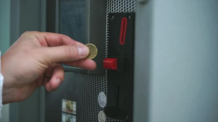 vending machine : Man dropping coin into vending machine, paying for something. Put money into a slot. Financial operation. Close up view