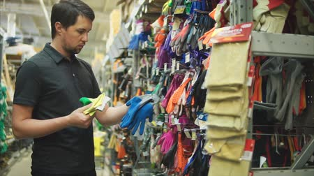 compares : Male customer in the hardware store choosing garden gloves. Man takes and compares two pairs of gloves.