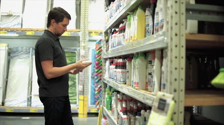dezenfektan : Man in the mall in department of household chemicals. He choosing cleaner sprayer and taking one of them from the shelf. Stok Video