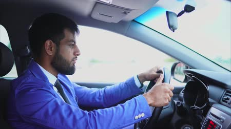 muslim leader : Muslim man in blue suit driving the car. Handsome serious businessman driving a car in the city
