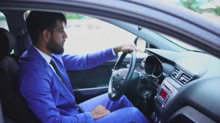 muslim leader : Handsome young muslim man driving the car and looking at the road. Modern muslim people. Stock Footage