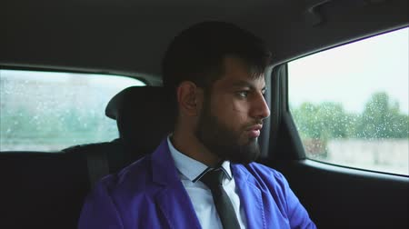 muslim leader : Young muslim businessman riding in the car on passengers seat. Rain outside the car. Passenger in taxi Stock Footage