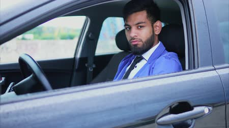 muslim leader : Handsome young muslim man sitting in the car and looking with piercing glance. Modern muslim people.