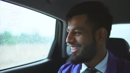 muslim leader : Close up view of young muslim man in the car. He sitting on the rear seat and looking through the window