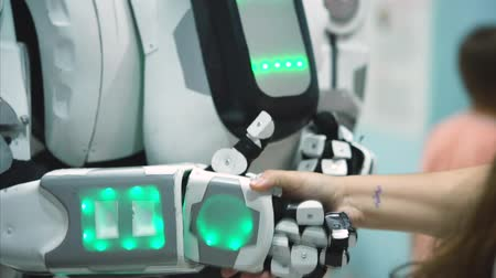automatizálás : Big robot shaking humans hand and giving high five. Humanoid antropomorf robot. Plaing with robot. Close up