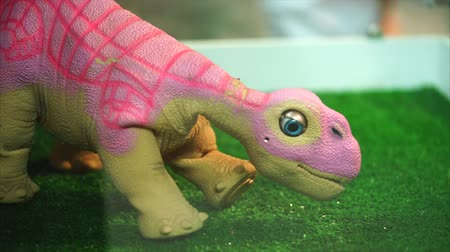 azman : Pink toy robot dinosaur moving his head and blinking his eyes. Concept of robotic toys and pets for children and adults.