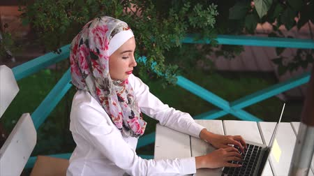 ислам : Young Muslim business woman working with laptop in outdoor cafe and representing modern lifestyle of Eastern women