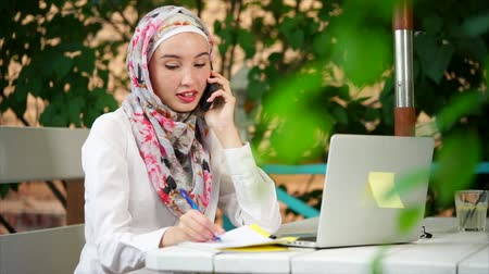 ислам : Young Muslim woman working in relaxing atmosphere of outdoor cafe. She talking on business and using laptop
