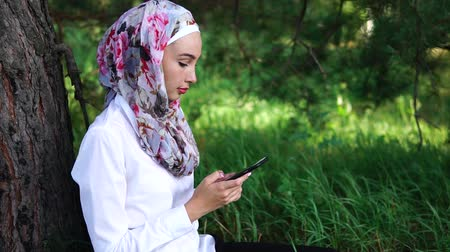 ислам : Cheerful Muslim girl in bright hijab sitting under the tree in the park and using mobile to surf internet or communicate