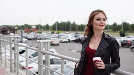 cityspace : A young woman with a make-up on her eyes, who smiles gently at the distance, the lady stands next to the car parking on the street in the summer or autumn day Stock Footage