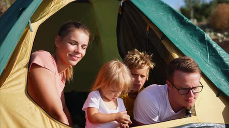 kamp : Family having great camping holidays. Happy mom, dad and two kids looking outside from the tent Stok Video
