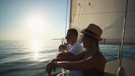 geniş açılı : Man and his woman are sitting on board a yacht and talking. They are watching sun meeting the river.