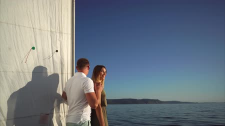 loved : Young couple of lovers is on a romantic boat with large white sail. They are looking to each other with love, touching hands and smiling. Stock Footage