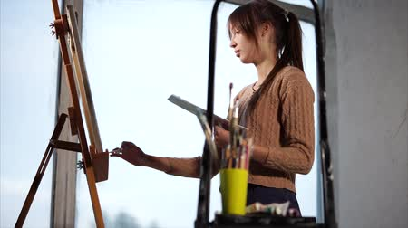 popisný : Young and very skillful artist is quitely drawing her painting indoor. She is painting by the window, there is an art supplies close to her.