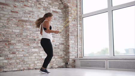 brickwall : Athletic woman is jumping rope wearing sportswear indoor. Sportswoman is training hard at the gym.