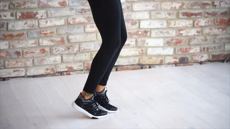 brickwall : Sportswoman is jumping rope in a fitness centre. She is wearing sportswear and black sneakers.