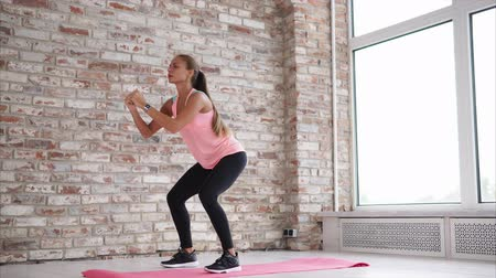 brickwall : Fitness woman squats on yoga mat in gym alone. She does one squat at a time going from left to right side.