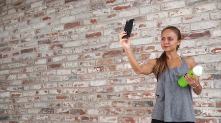 brickwall : After an intense training woman takes selfie by the brick wall in the gym. She is wearing sportswear and holding bottle with water. Stock Footage