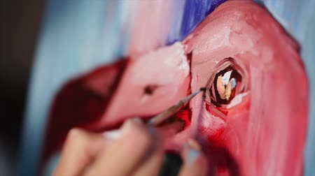 cobalt : Artist is painting an eye and beak of pink flamingo by oil paints on a canvas. Close-up shot of her hand, holding paintbrush, in workshop.