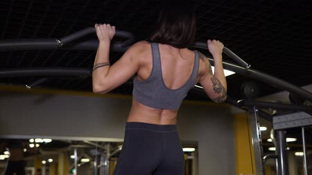 definição : Athletic woman with tattoos is doing an exercise for her back in gym. She is doing clear pullups.