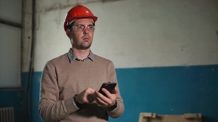 compares : An adult man in a helmet who holds a smart background in his hand works as an engineer, the person compares the readings via the Internet on a gadget