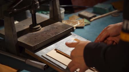 presser : Professional leathersmith takes wooden plate with a leather and remove from under the press. He removes metal form and looks on a left mark on leather. Stock Footage