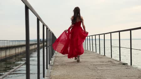 mar vermelho : a young woman with long curly hair running quickly down the pier along the ocean or the sea, the lady is late and tries to hurry to see the seascape