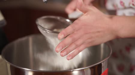 sifting : close up shot of the chefs hand, who holds the sieve and with his help sifts the flour into a bowl from an electric mixer, the lady will beat the players